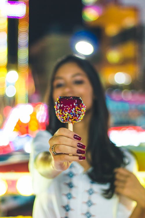 Selective Focus Photo of Woman Holding Out a Candy Apple