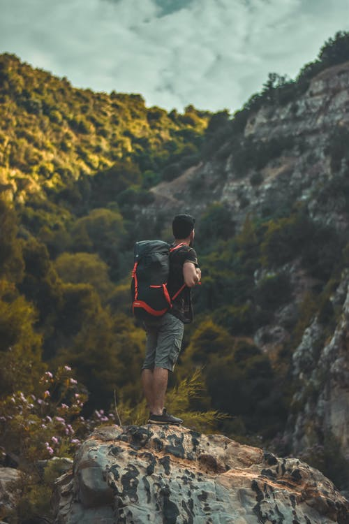 Man in Black T-shirt Carrying a Bag-pack Standing on Cliff