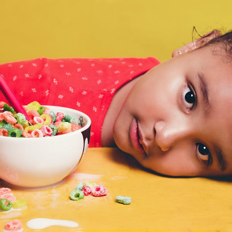Girl Wearing Red Shirt Lying on table Beside White Bowl With Cereal