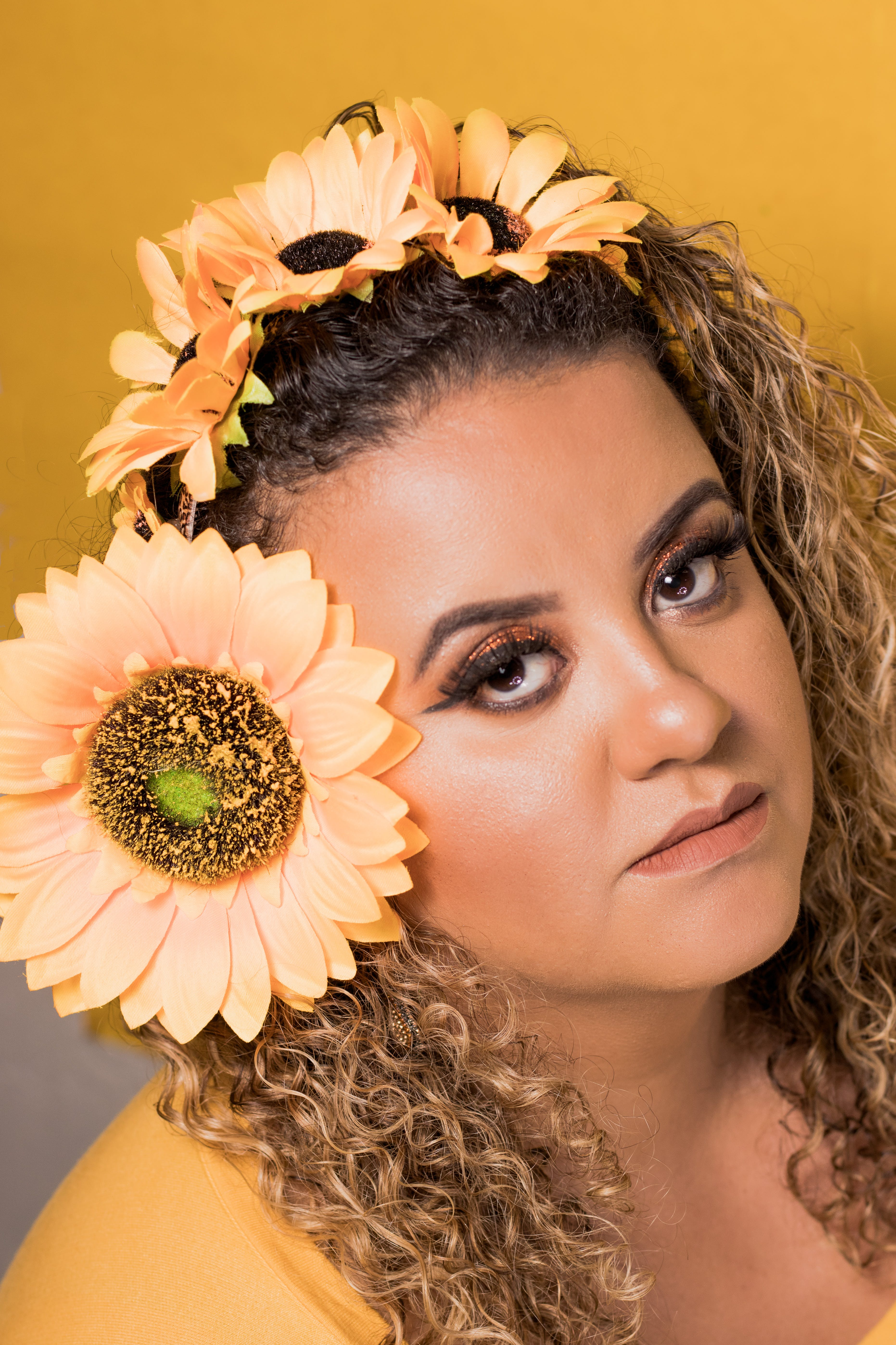 Photo of Woman in Yellow Top With Sunflowers on Her Hair