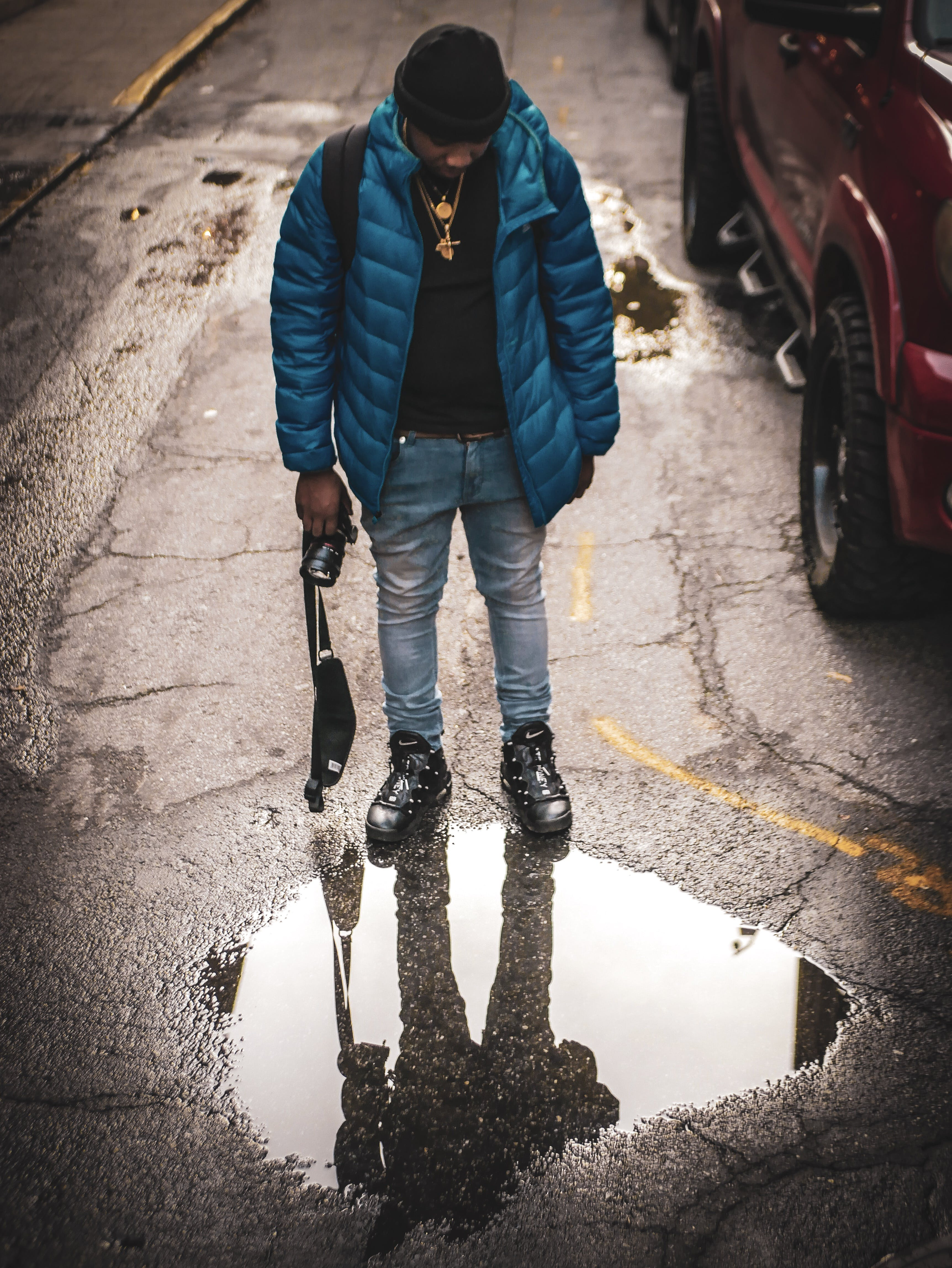 Man Looking on Puddle on Road