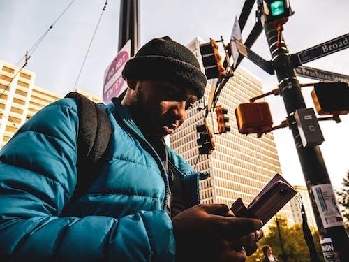 Man Wearing Bubble Zip Jacket Using Smartphone