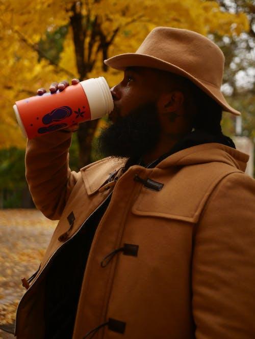プラスチック製のタンブラーから飲む茶色の帽子と茶色のアウターウェアの男の写真