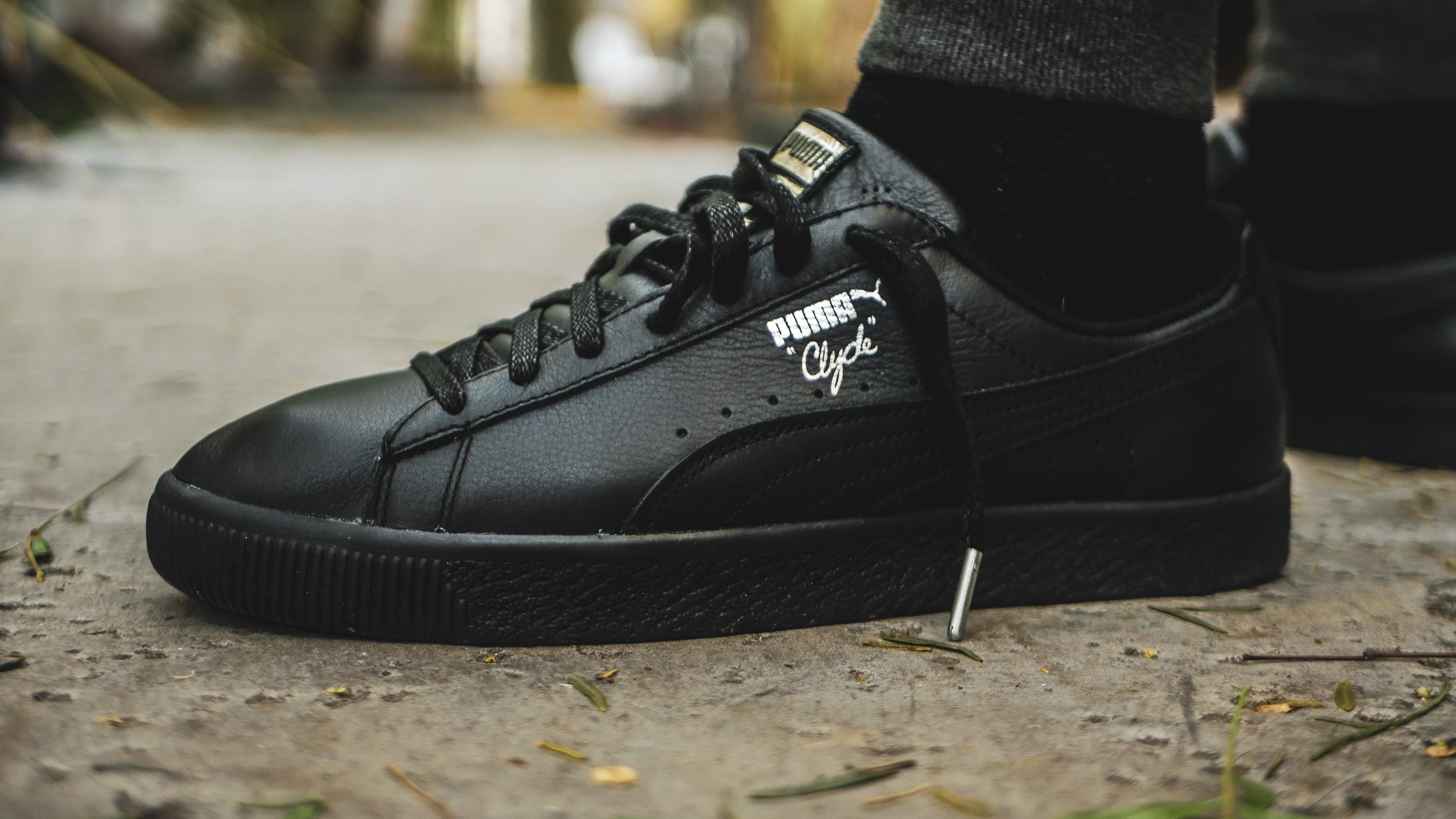Person Wearing Black Puma Low-top Sneakers