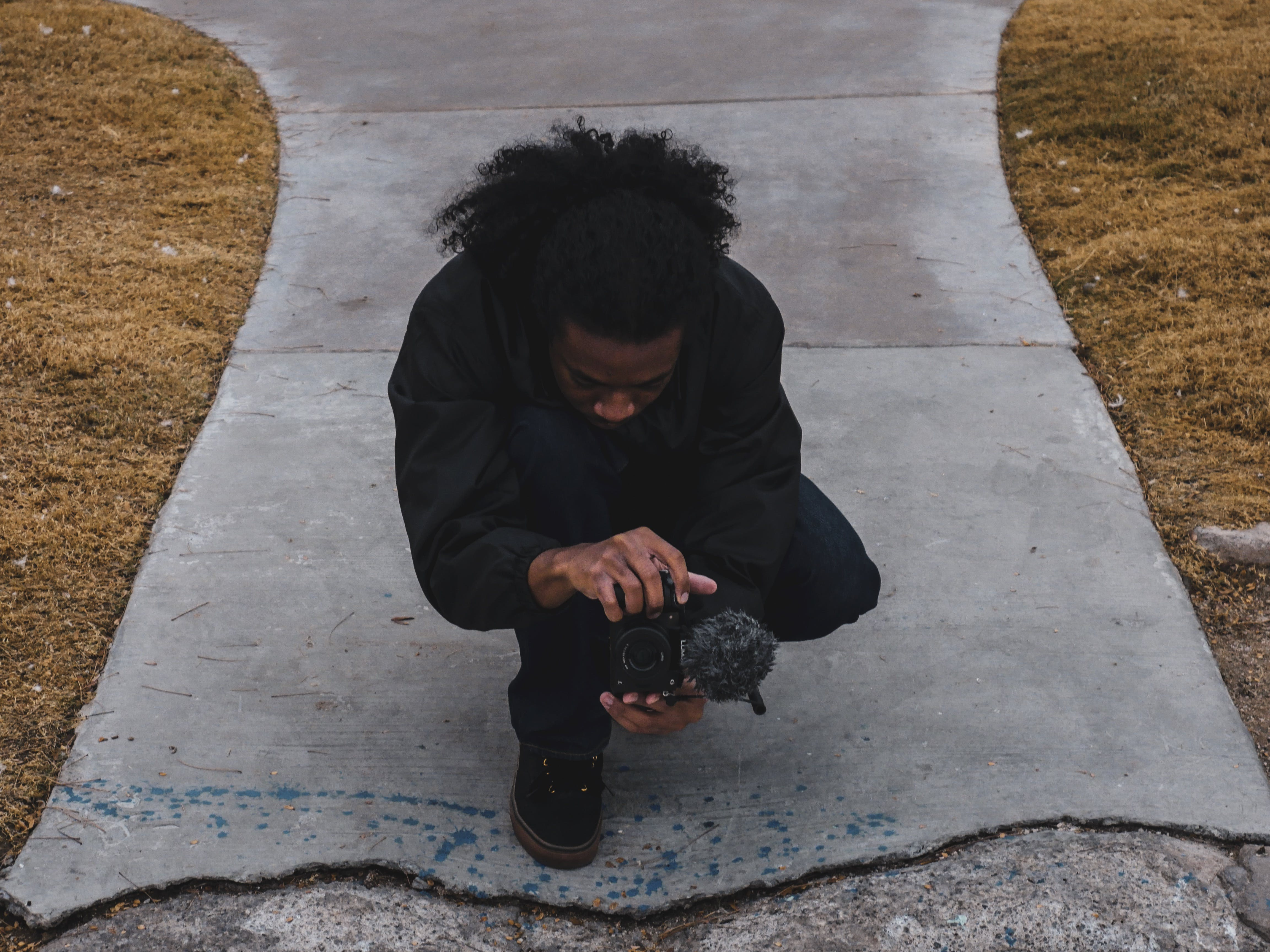 Man Crouching Holding Camera