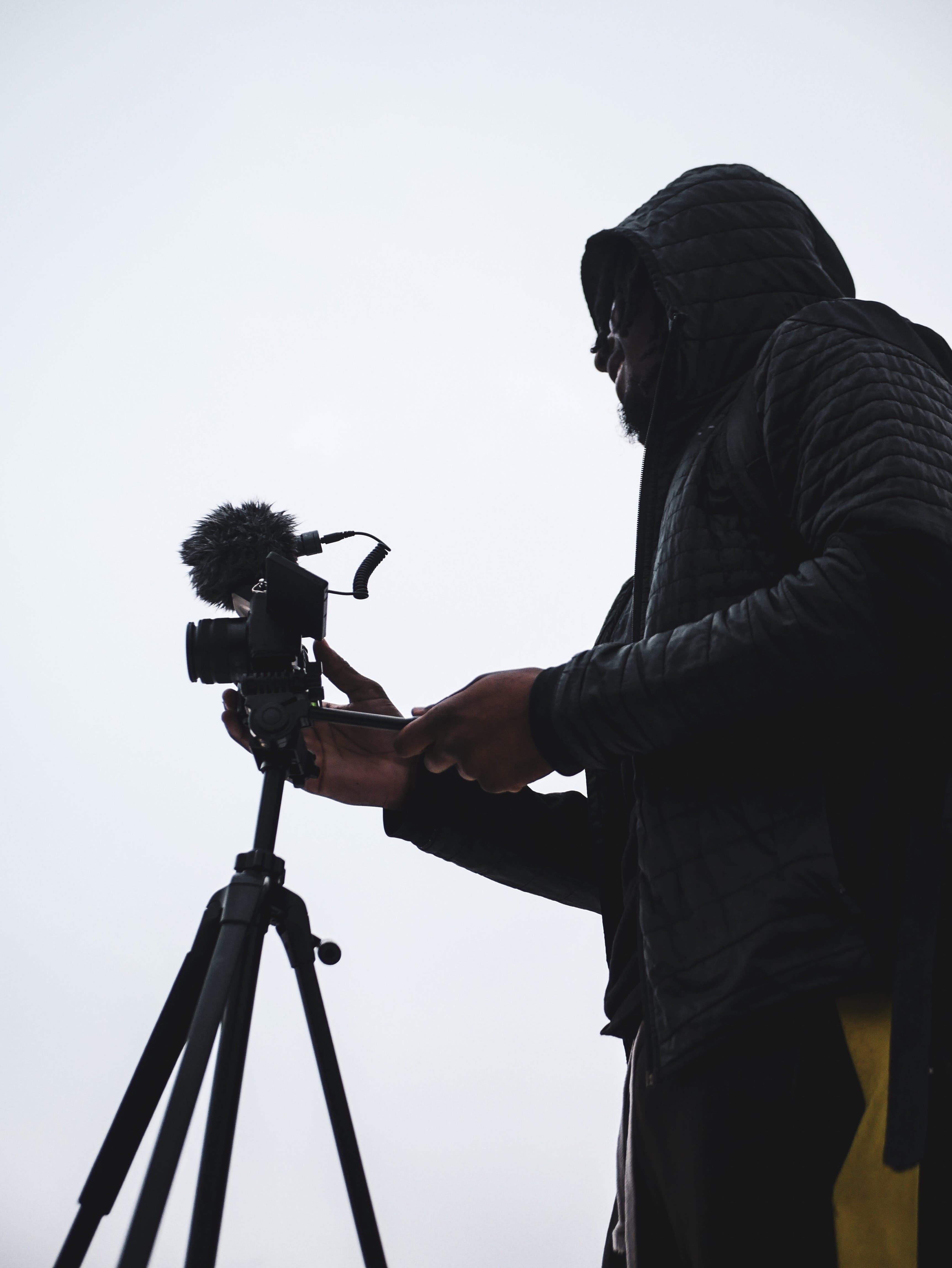 Person Holding Camera on Tripod