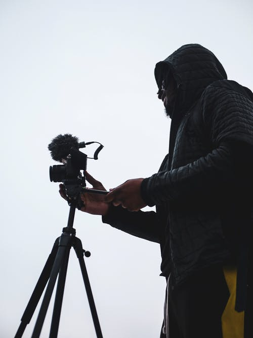 Person Holding Camera on Tripod