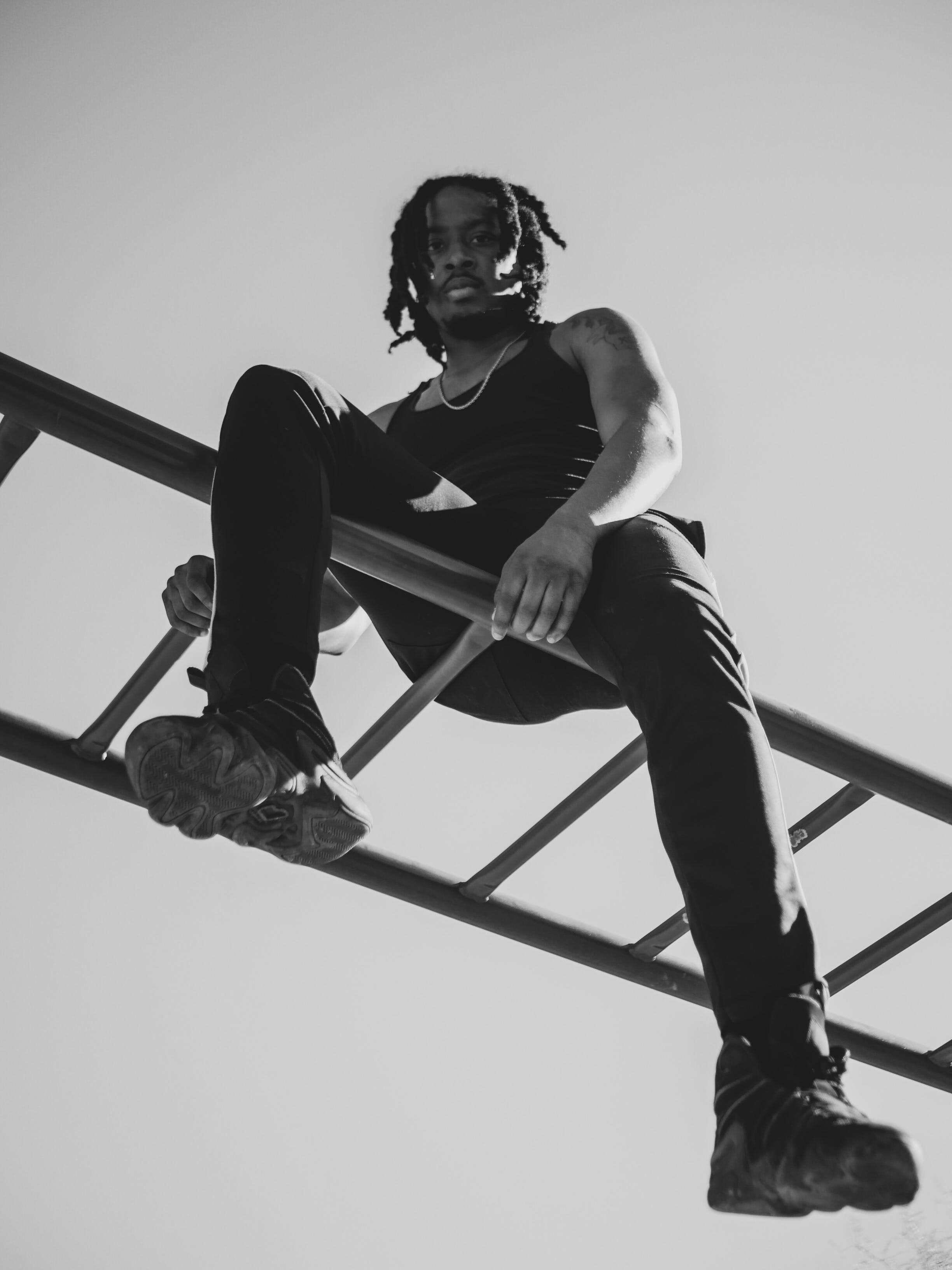 Monochrome Photo of Man Sitting On Horizontal Ladder