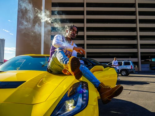 Photo of Man Sitting on Yellow Corvette Stingray