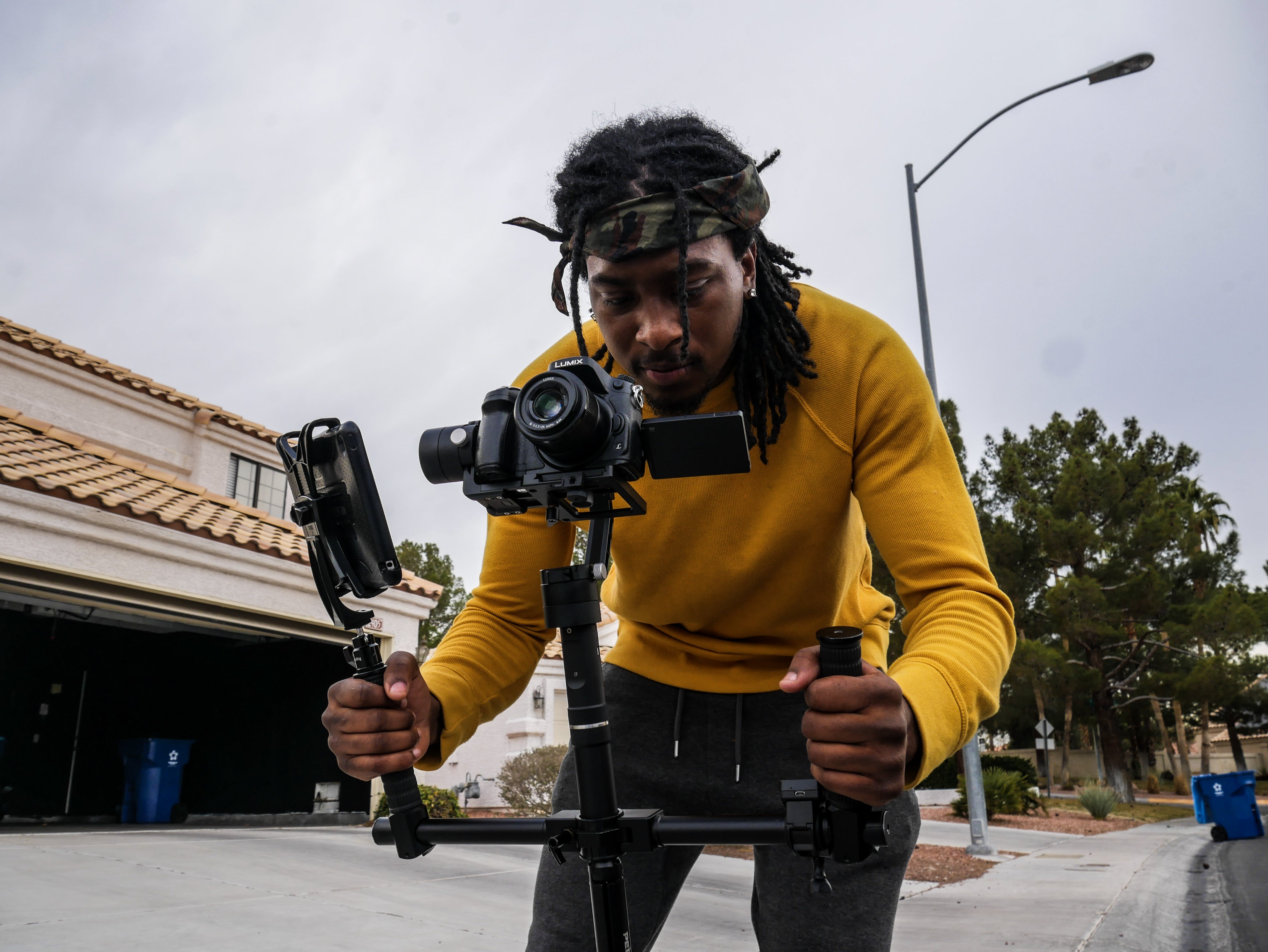 Man Wearing Yellow Long-sleeved Shirt Holding Camera Stand