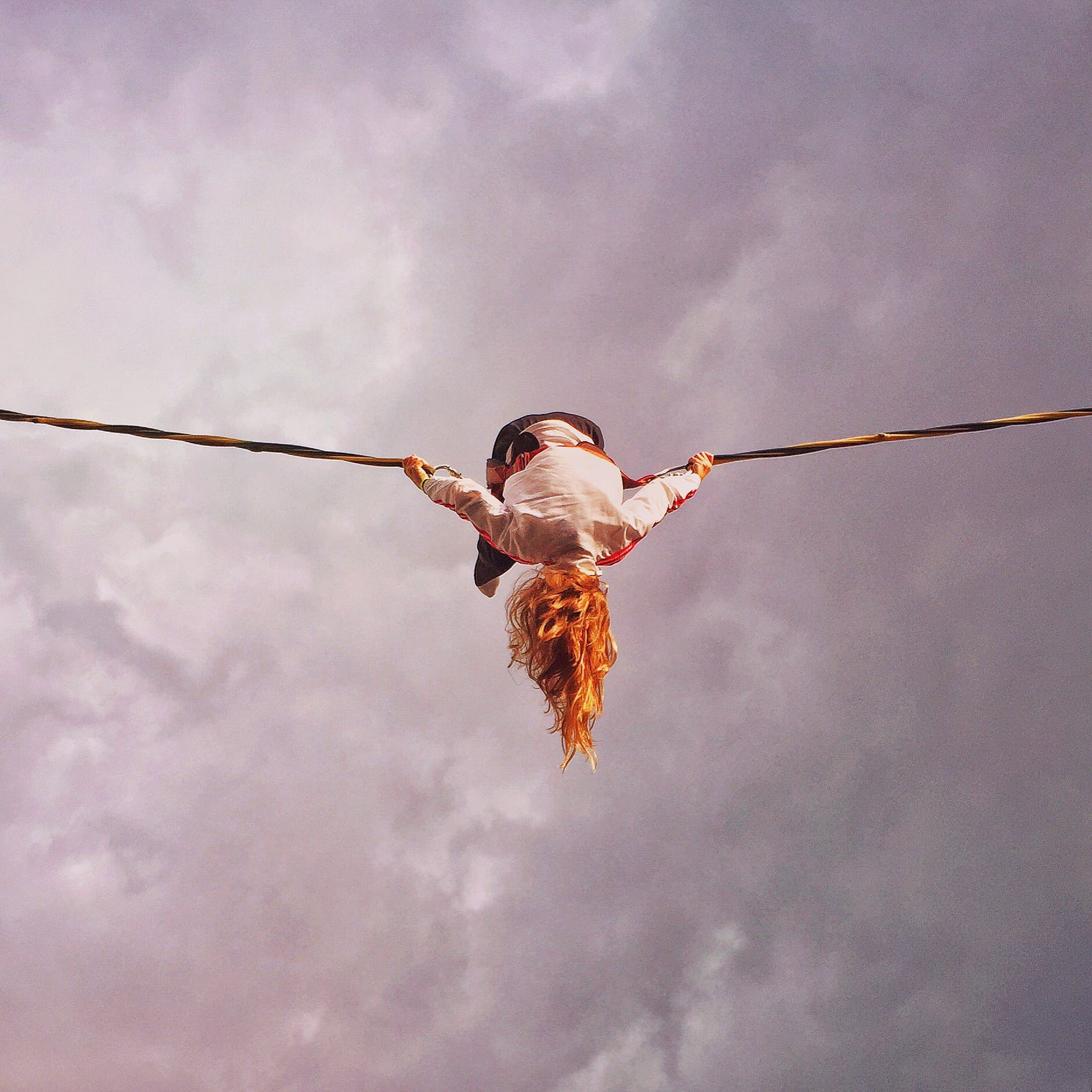 Girl With Orange Hair Flipping While Holding Rope