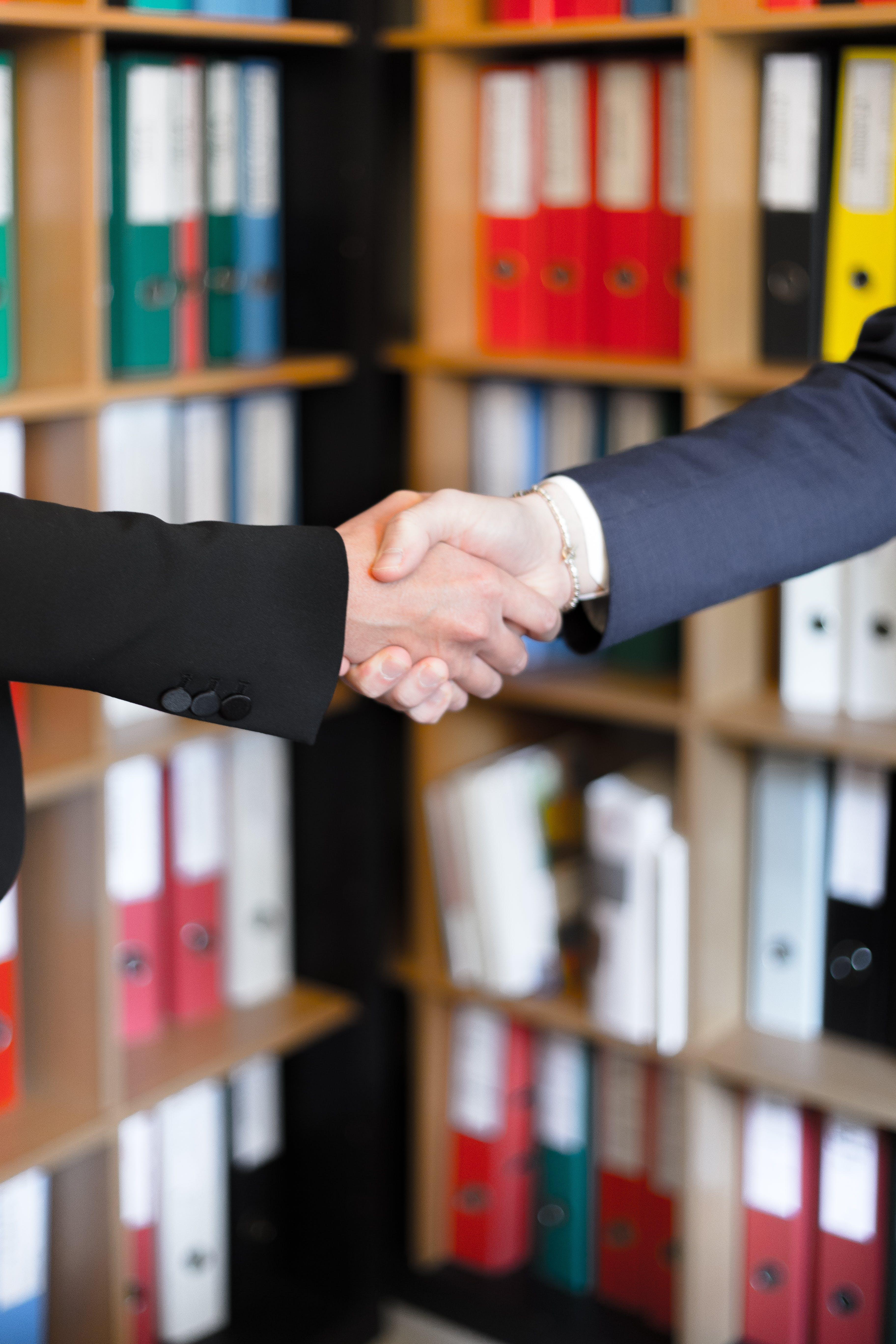 anlaşma, el sıkışma, iş birliği, kitaplık içeren Ücretsiz stok fotoğraf