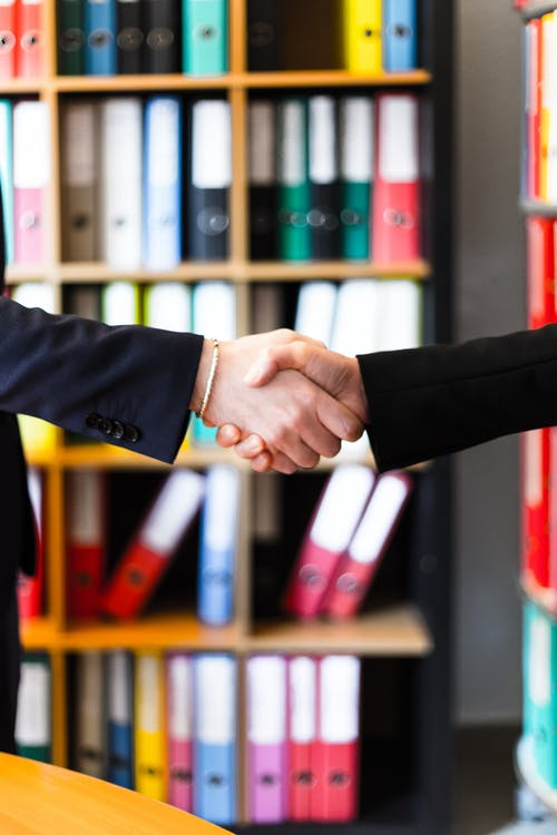 Two Person Handshakes in Front of Books on Shelf