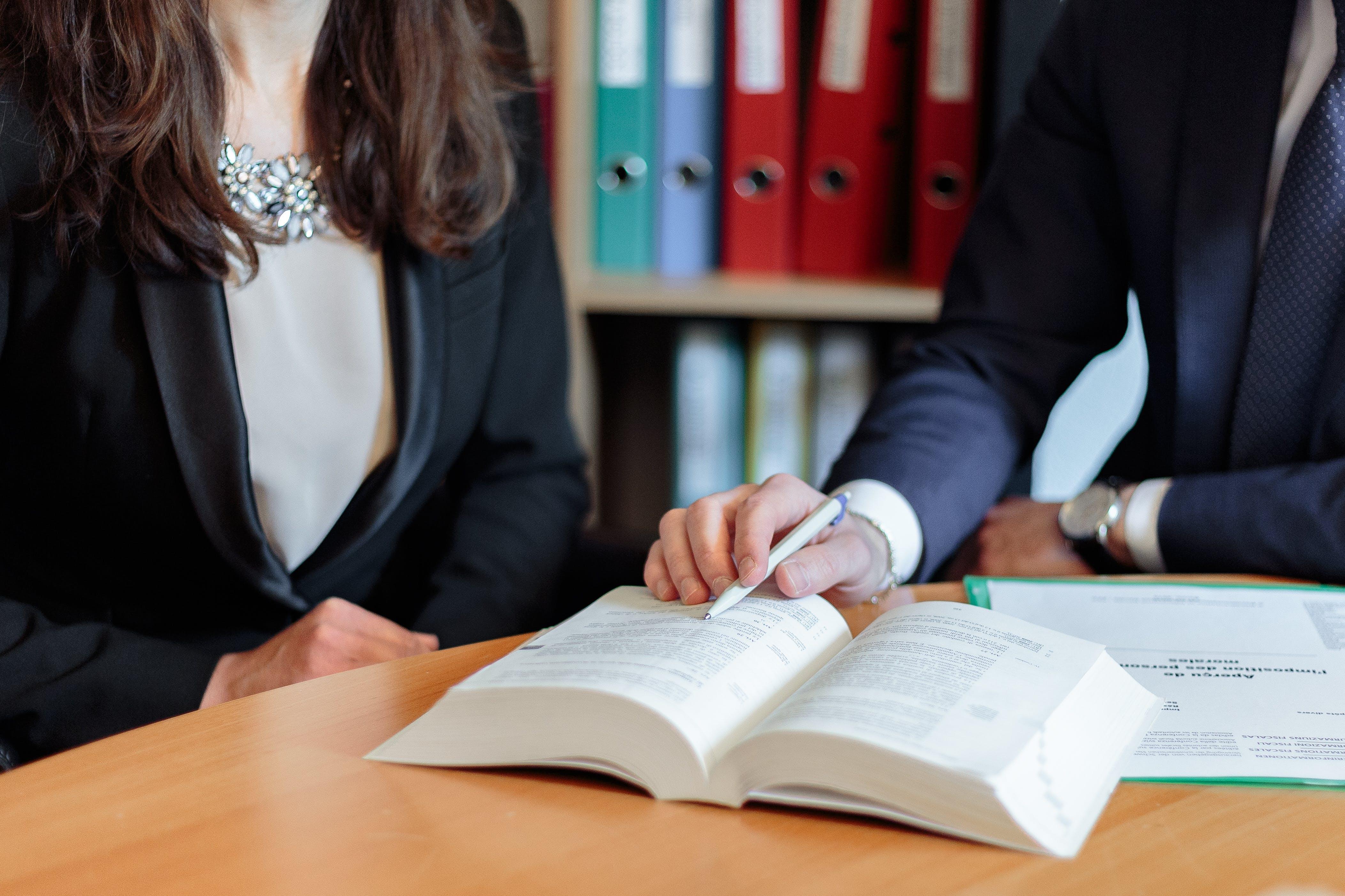 Man and Woman Sitting Facing Book