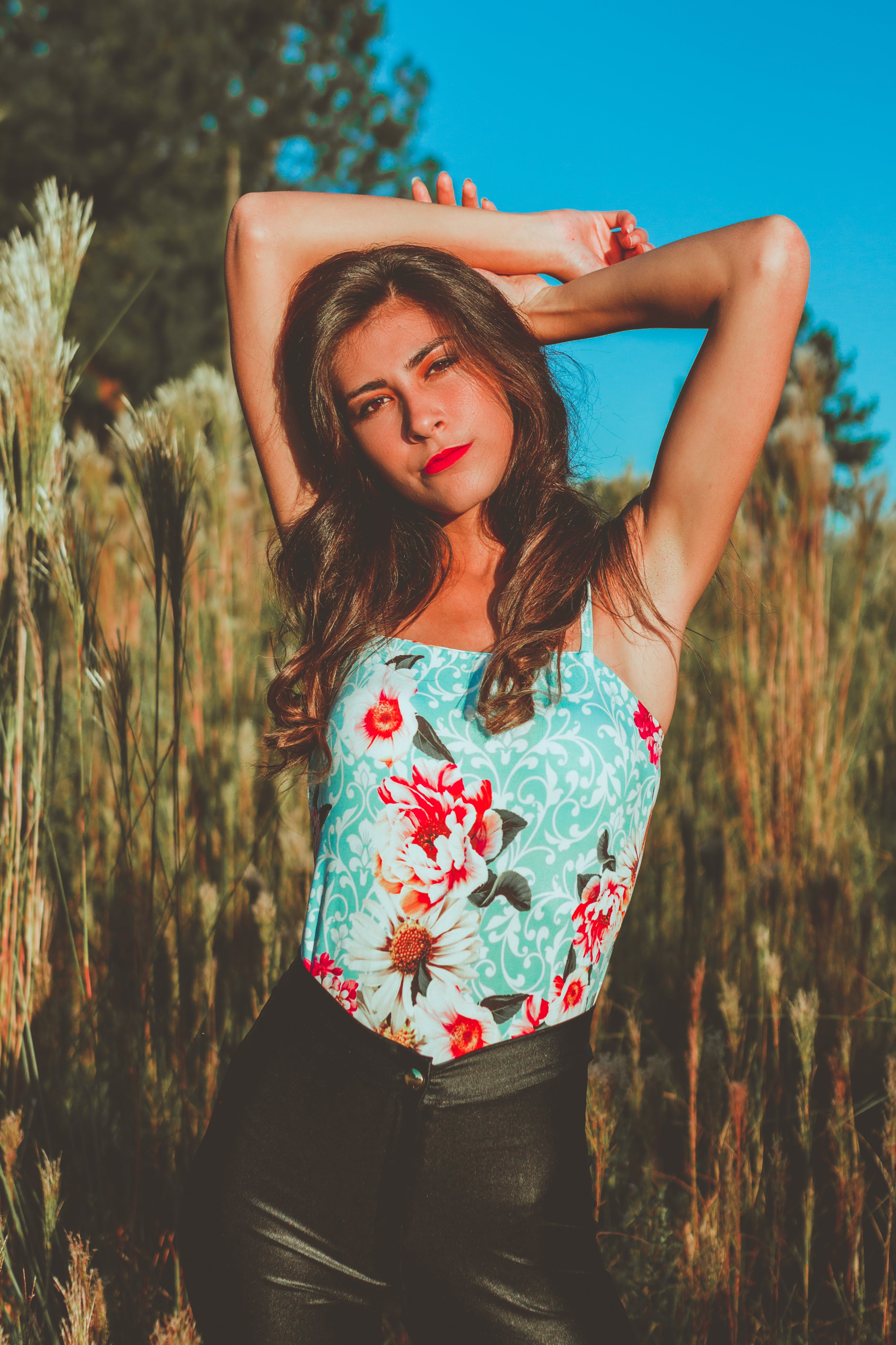 Woman In Teal And Red Floral Top Standing On Grass Field