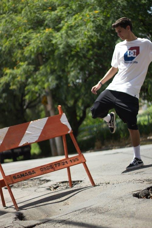Man in White Crew Neck Shirt Kicking on Signage