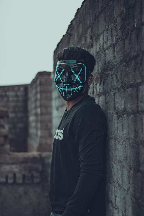 Man Wearing Mask Leaning On Wall