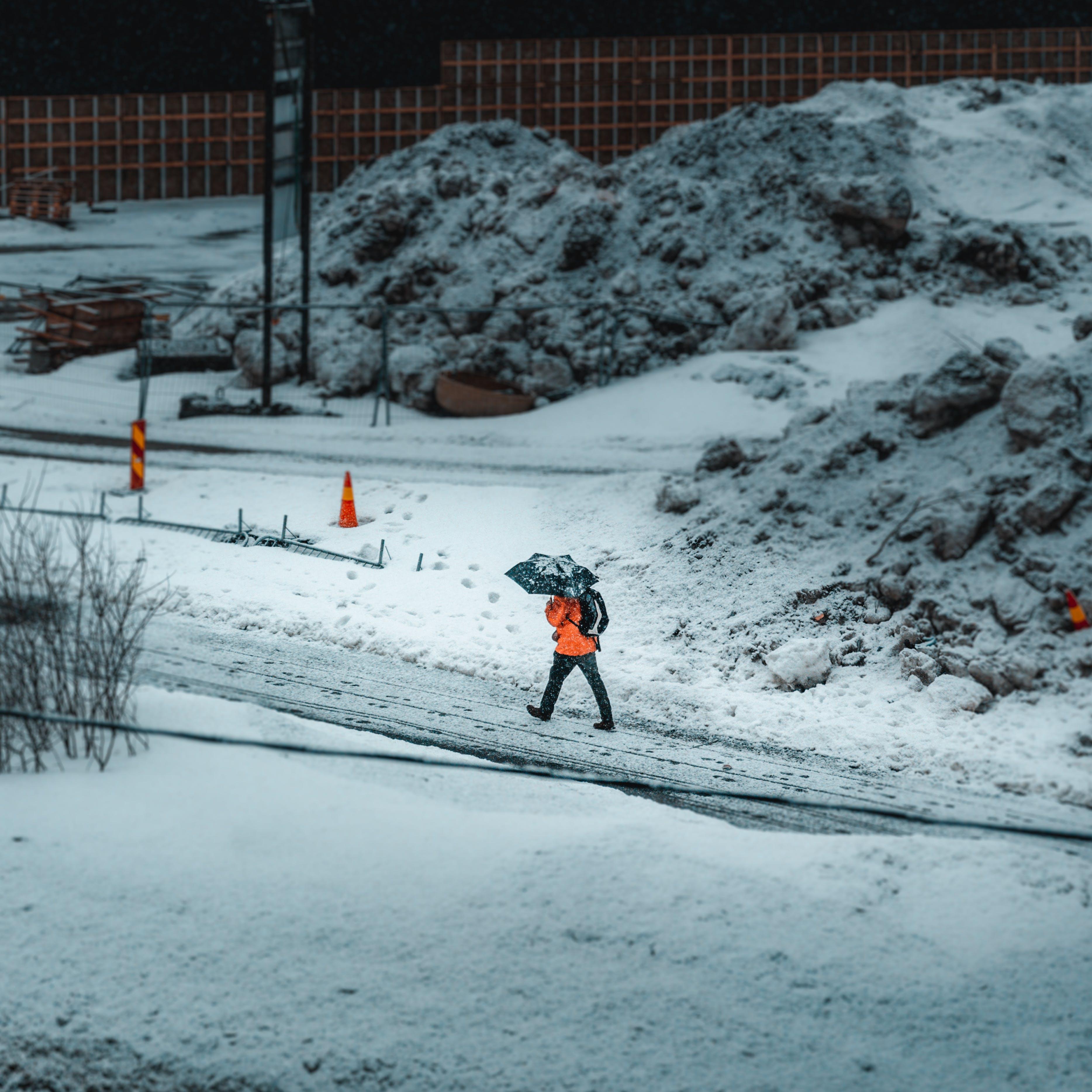 Man Walking Near Traffic Cones