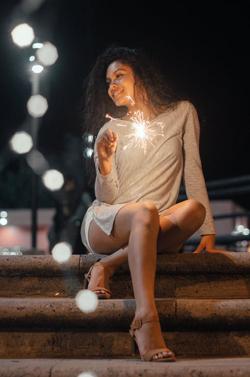 Woman Sitting On Concrete Stairs Holding Sparkler