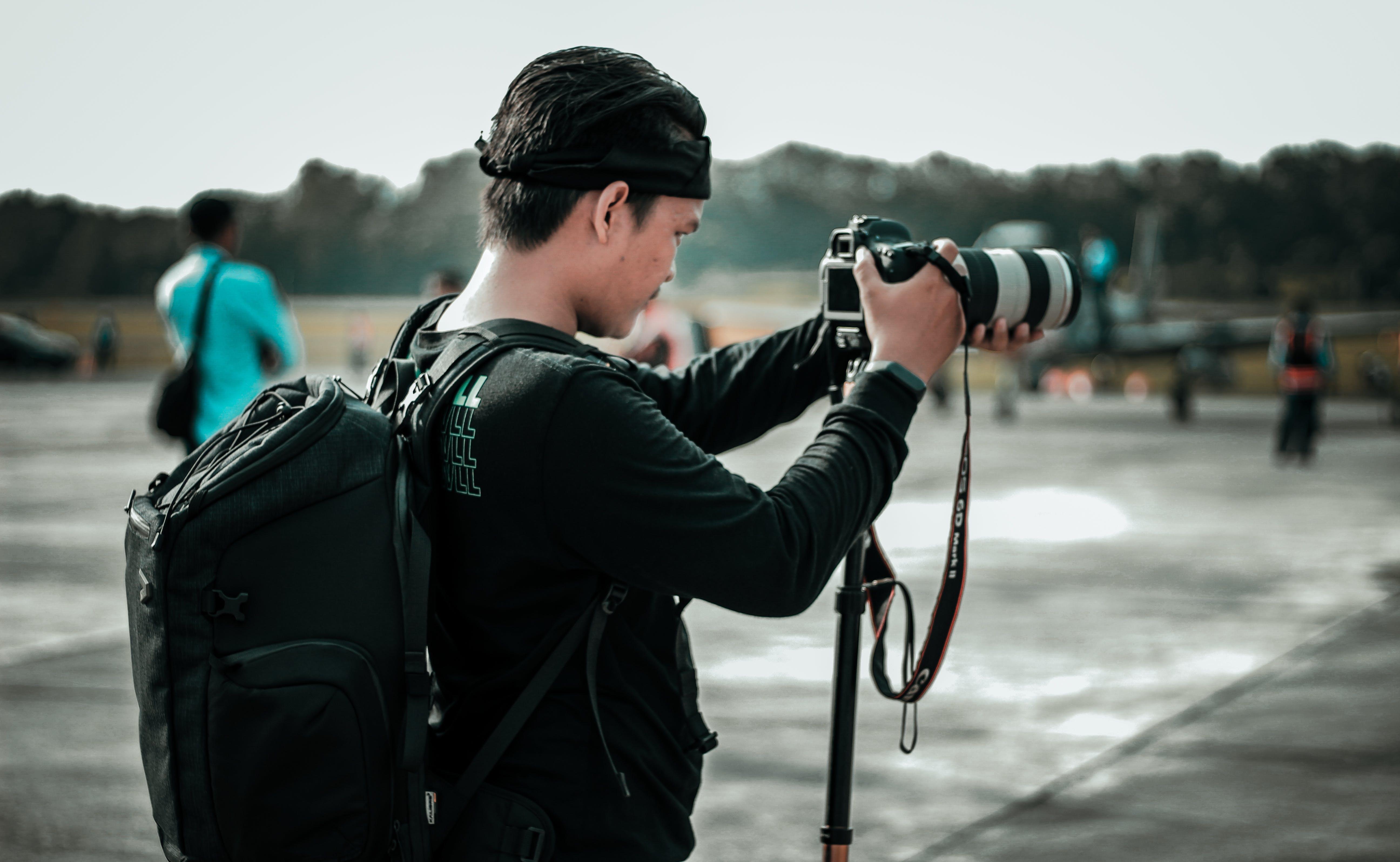 Focus Photography of Man Using Dslr Camera