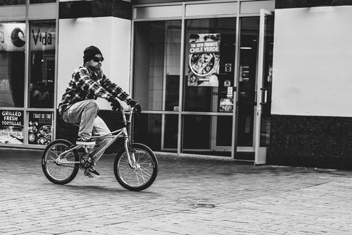 Grayscale Photography Of Man Riding Bike