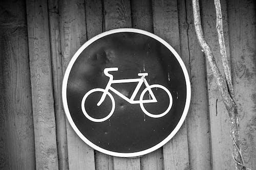 Foto d'estoc gratuïta de blanc i negre, de fusta, mur, rètol de bicicleta