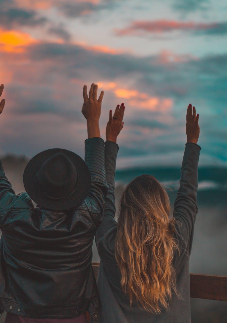 man and woman rising both arms