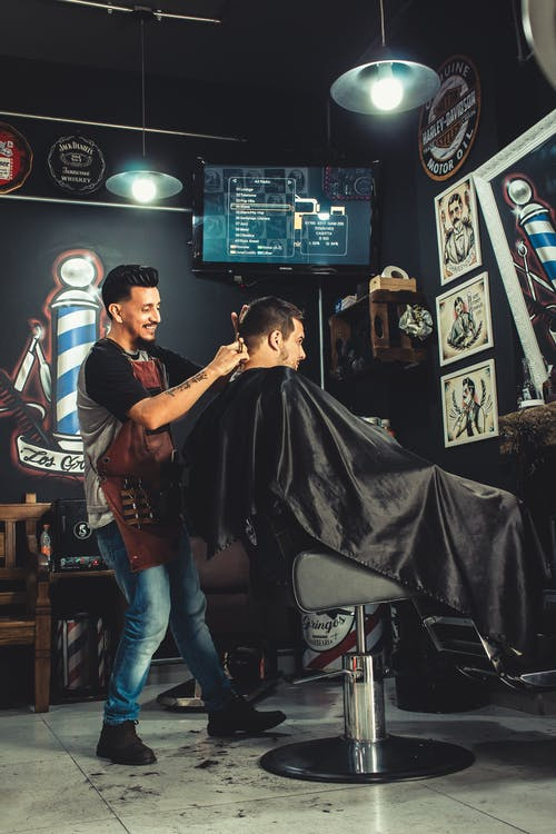 Smiling Man Cutting Another Mans Hair Inside Shop