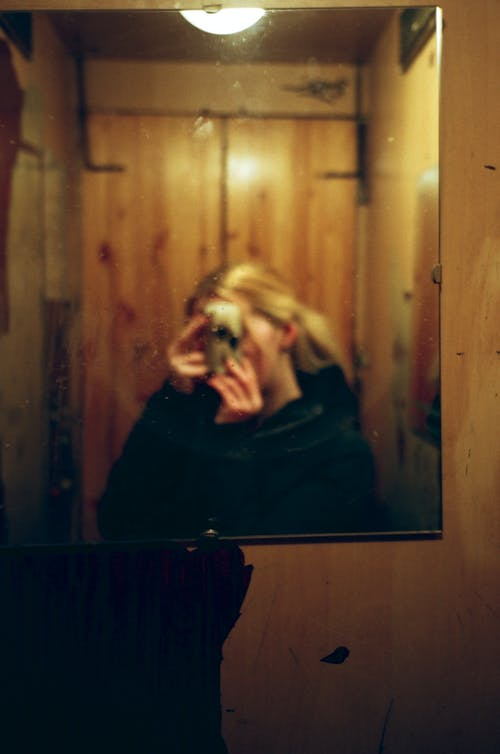 Woman Taking Picture in Front of Mirror