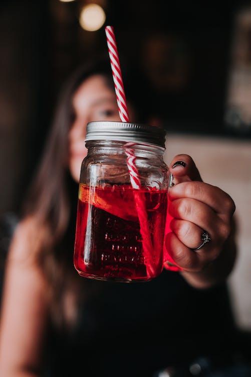Woman Holding Red Glass Mason Jar