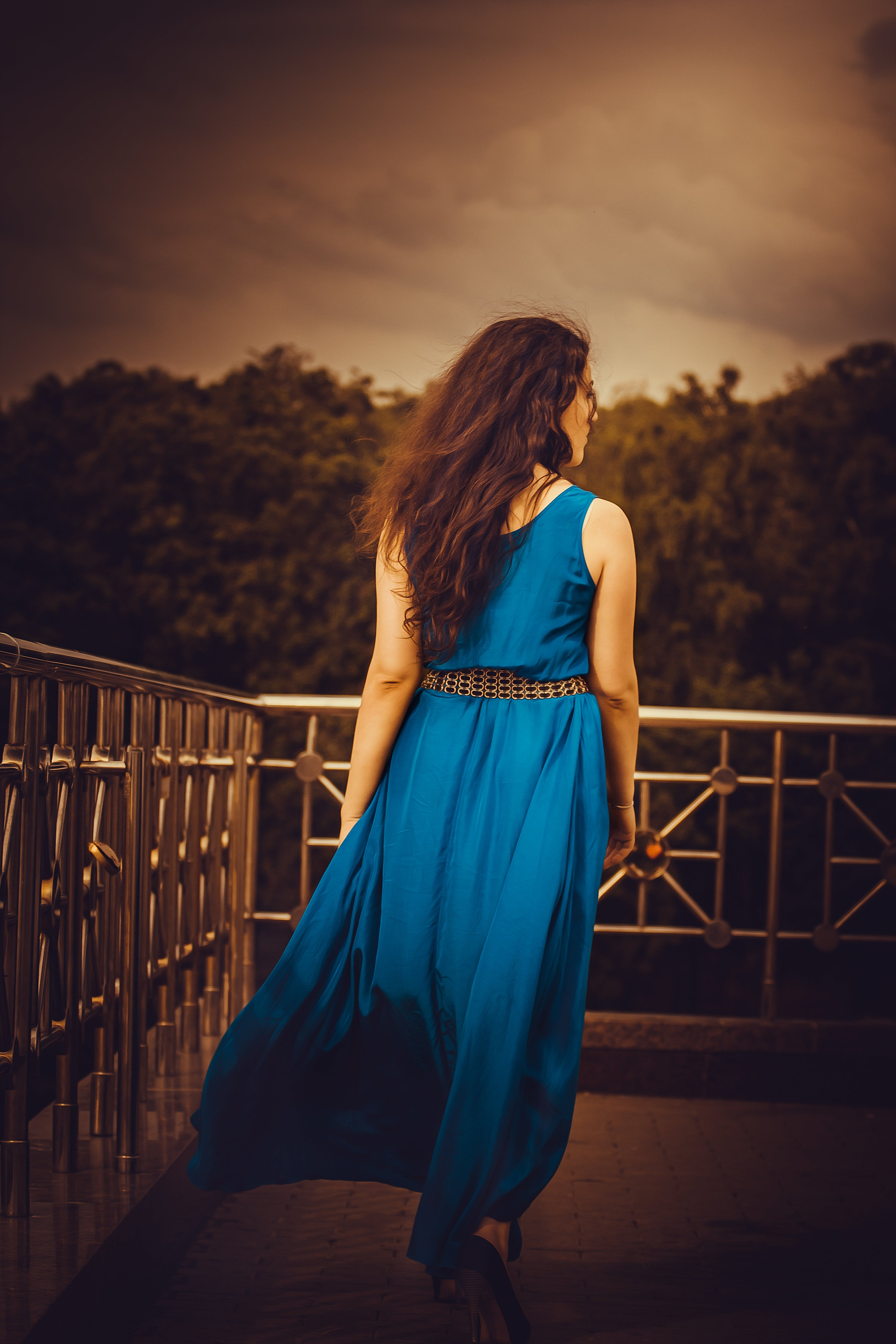 Woman Facing Away Wearing Blue Tank Long Dress Looking Out to Trees