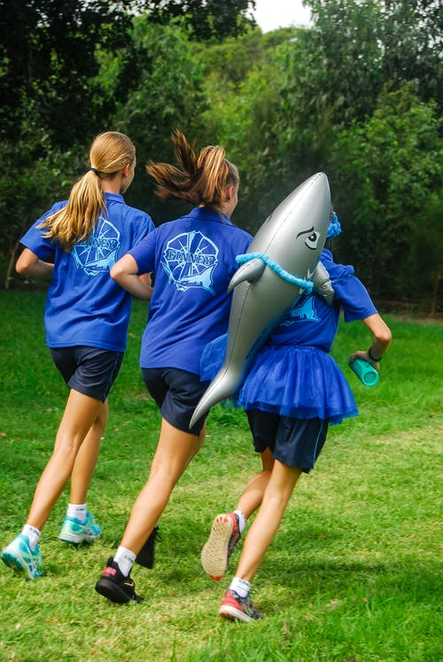 One Girl Carrying Shark Balloon Running With Two Girls in Blue Uniforms