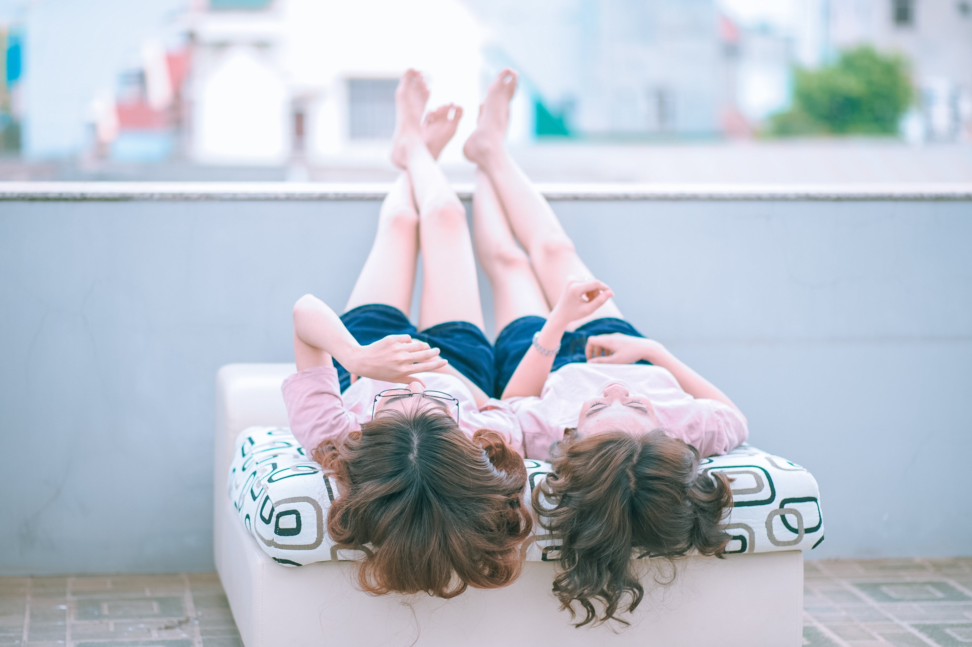 Two Girl Lying on Sofa While Looking Up