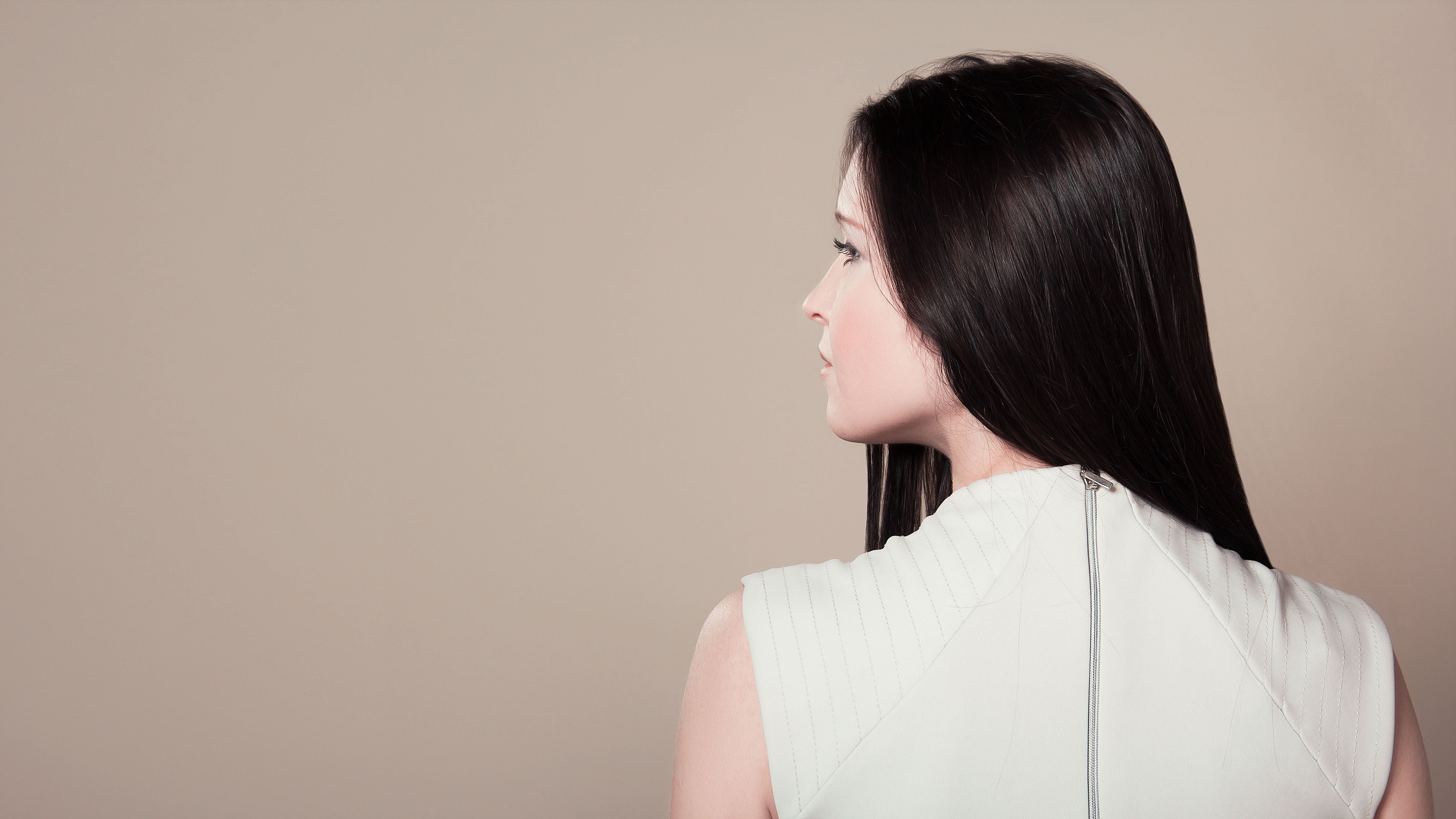 Woman in White Sleeveless High Neck Top Showing Her Back