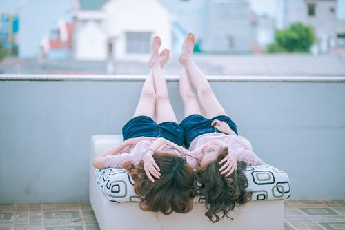 Two Woman Wearing Pink Shirt and Blue Shorts Lying on Sofa Facing Each Other While Both Feet Crossed and Placed on Concrete Wall