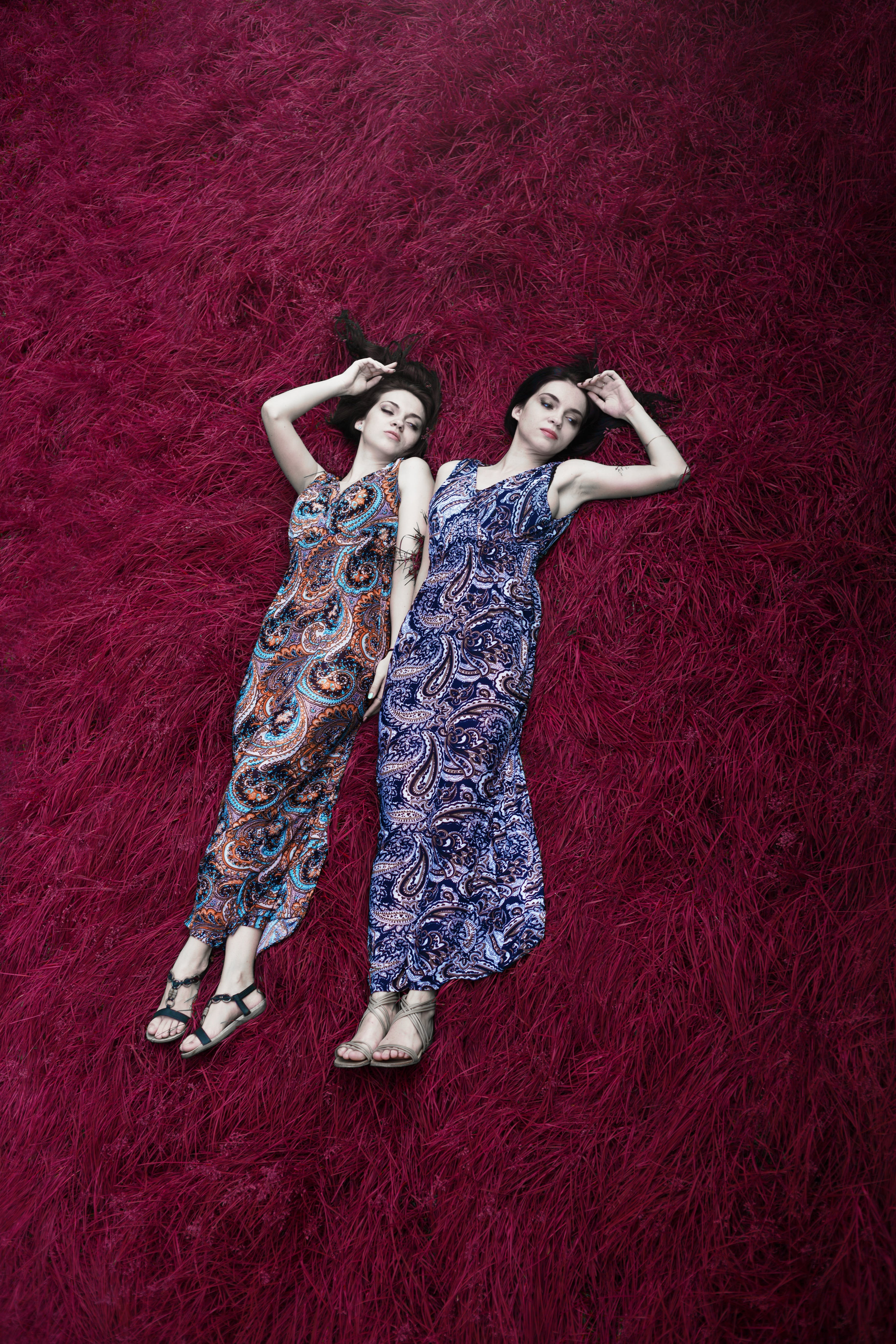 Two Women Lying on Red Surface