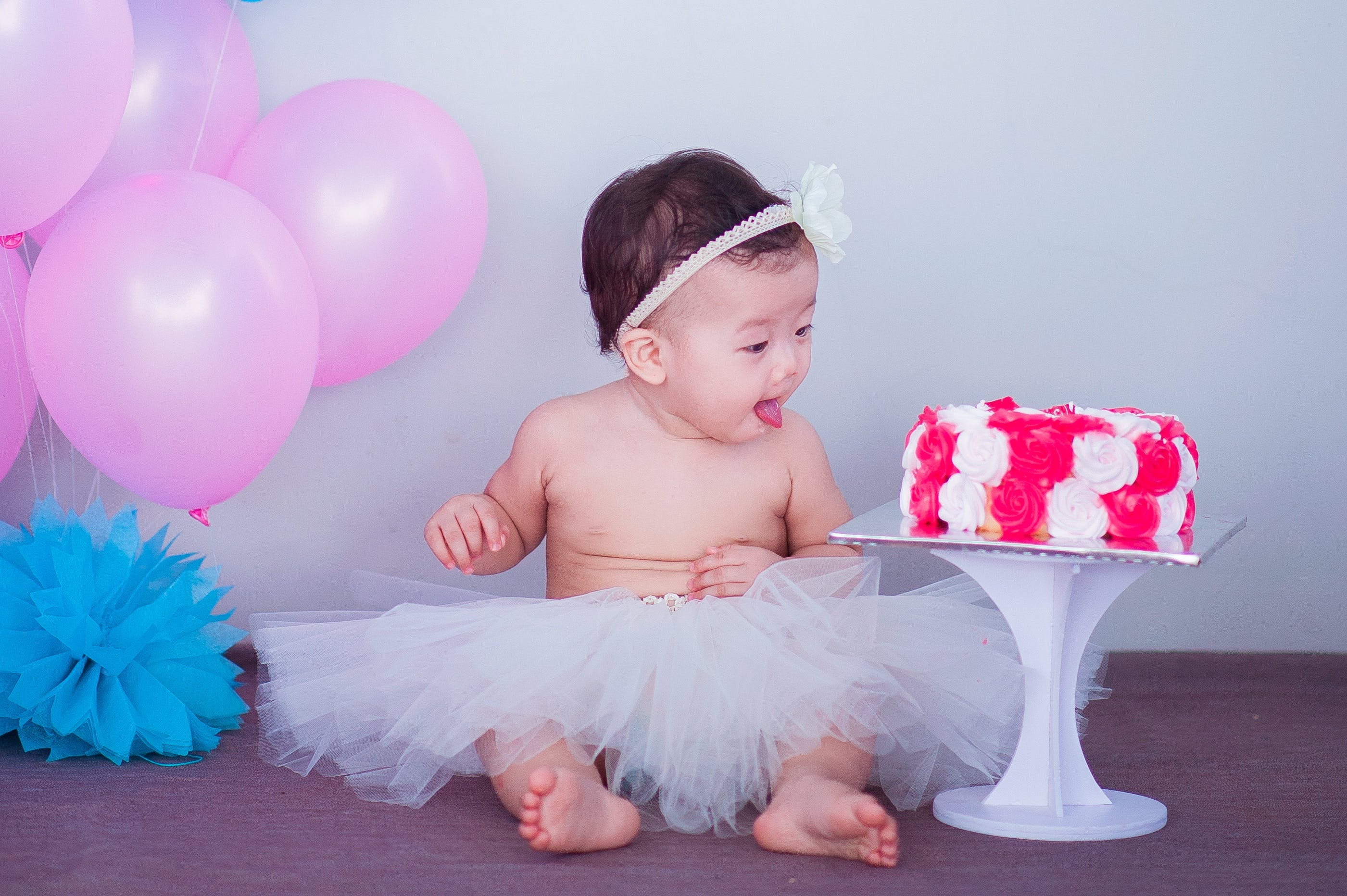 Baby in White Tutu Skirt Beside Cake