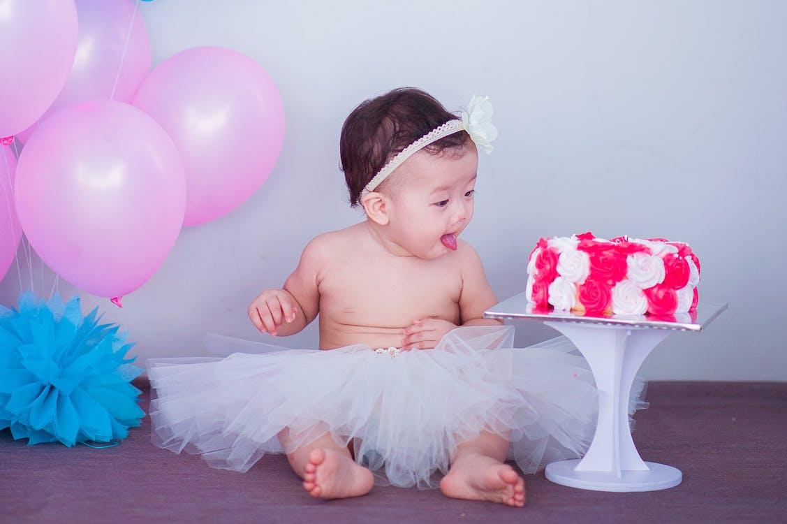 Baby in White Tutu Skirt Beside Cake