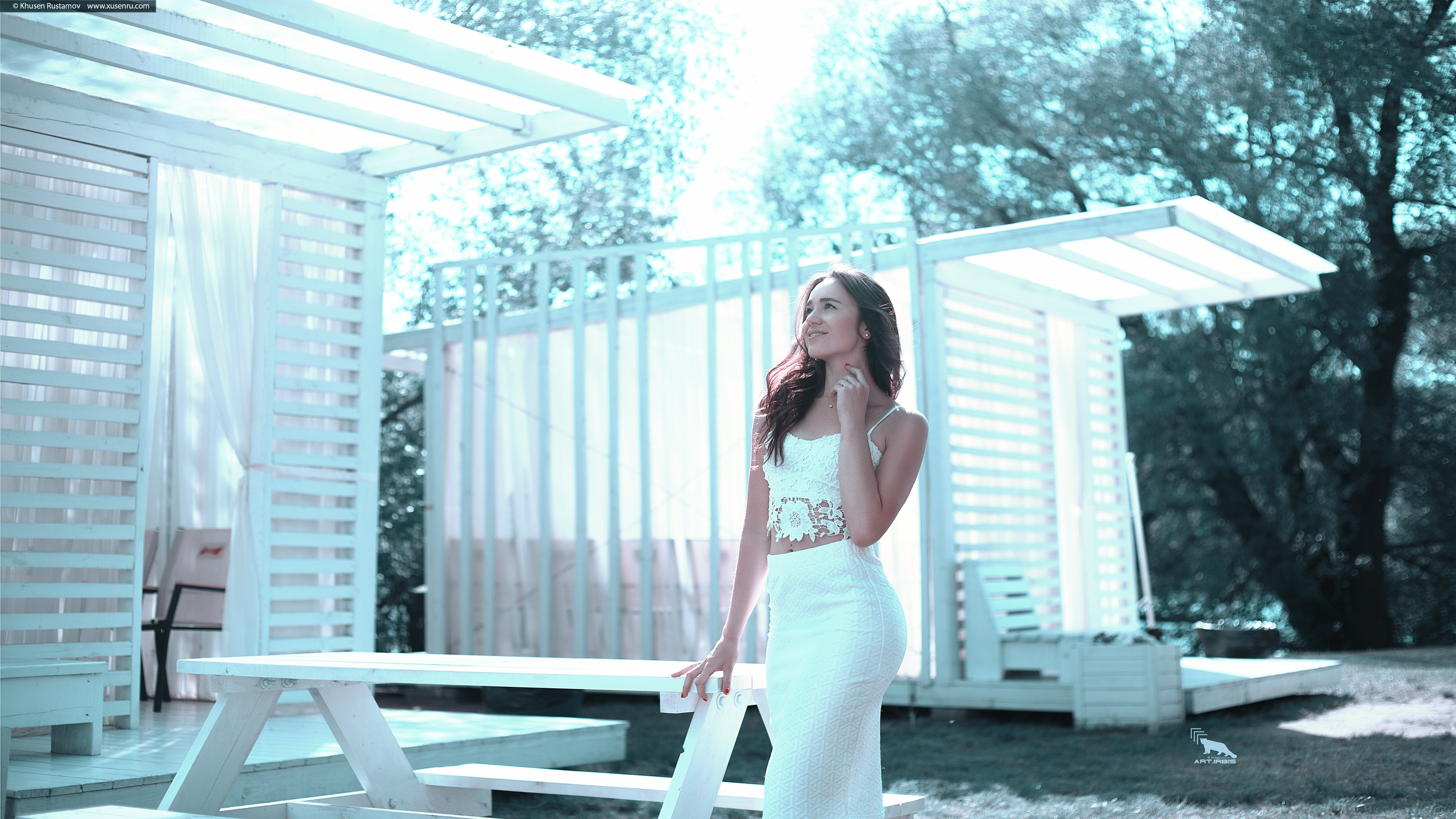 Woman in White Dress Standing Beside White Wooden Picnic Table