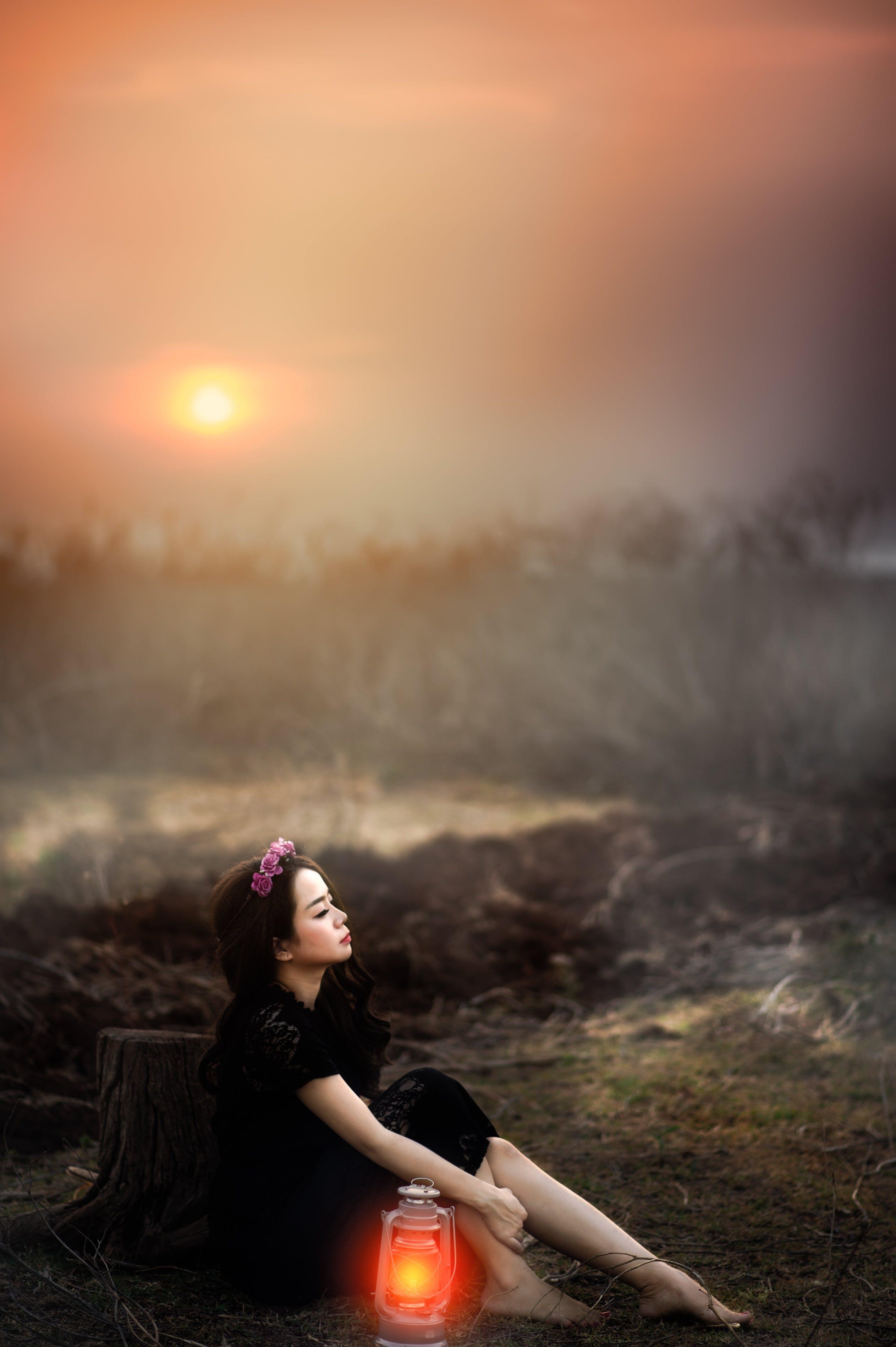 Woman Sitting Beside Lit Lantern