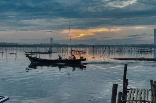 Foto d'estoc gratuïta de aigua, barca, barca de pesca, capvespre