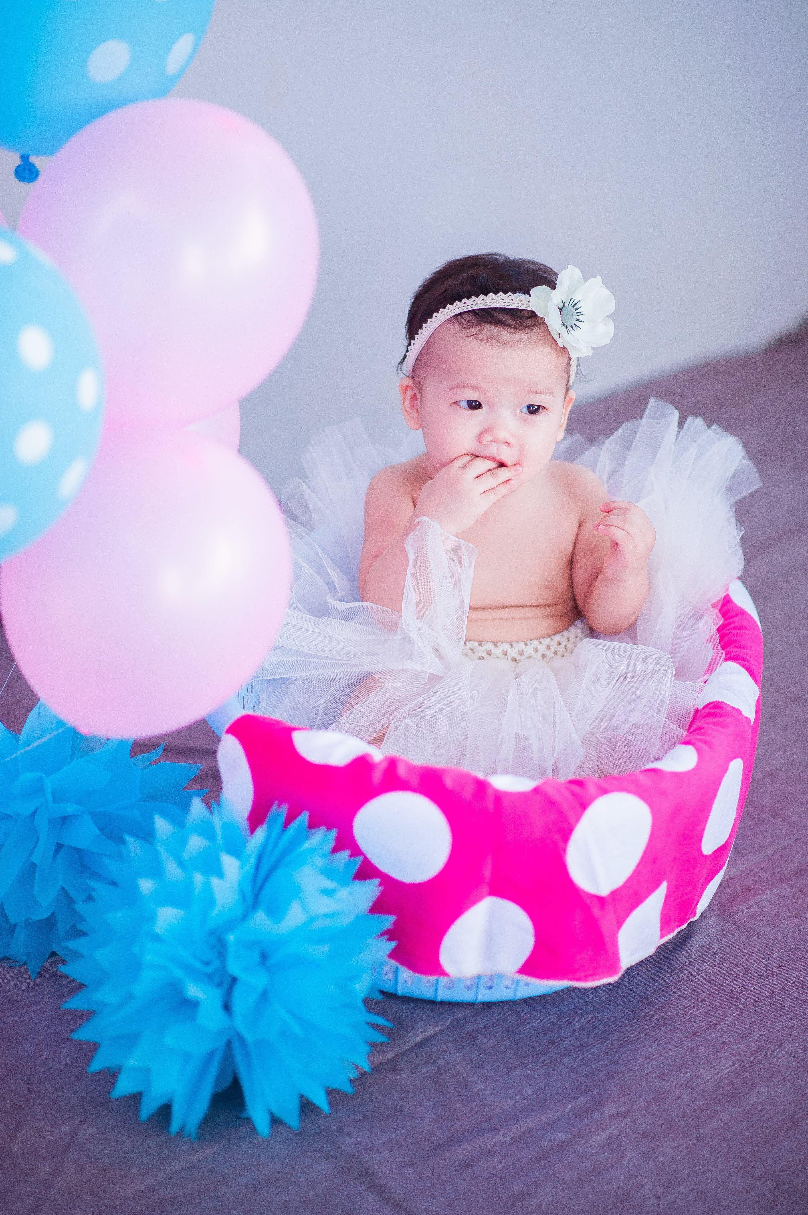 Baby Sitting on White and Pink Polka-dot Basket With Balloons