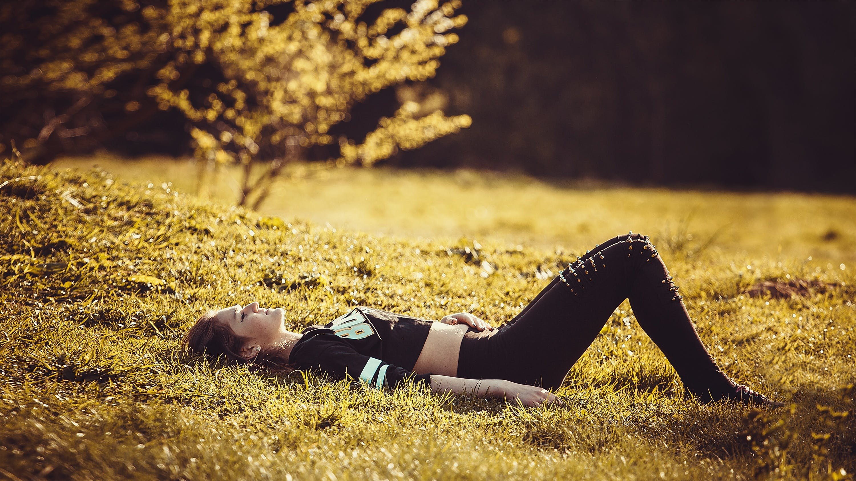 Woman Lying on Grass during Day