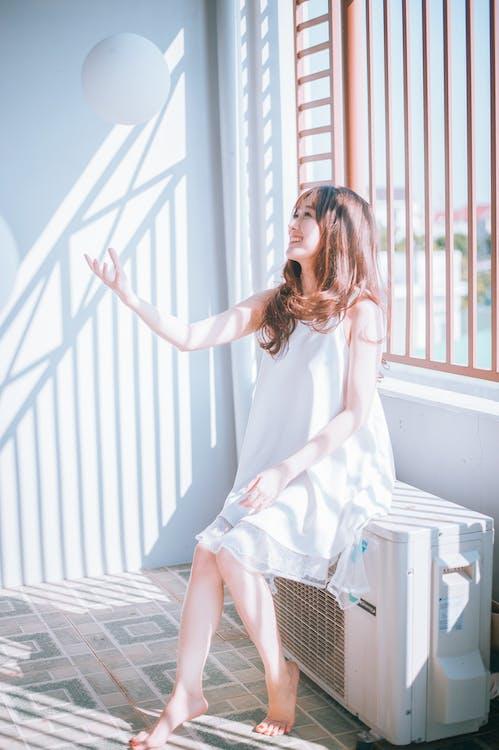 Woman Sitting on White Air Condensing Unit Near Window
