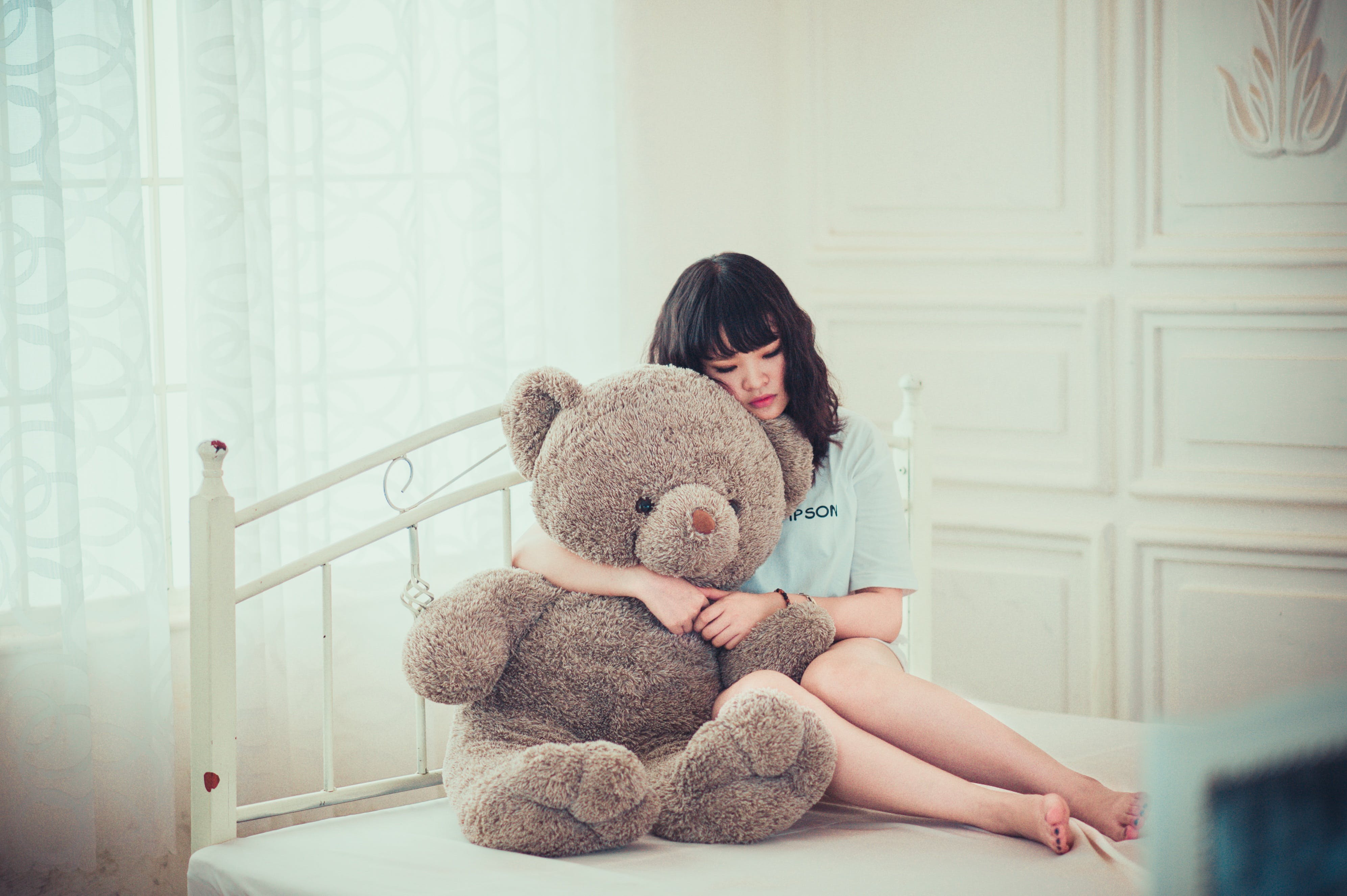 Woman Hugging Gray Bear Plush Toy on White Mattress