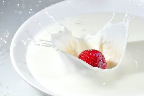 Time Lapse Photography of Strawberry Falling on Milk