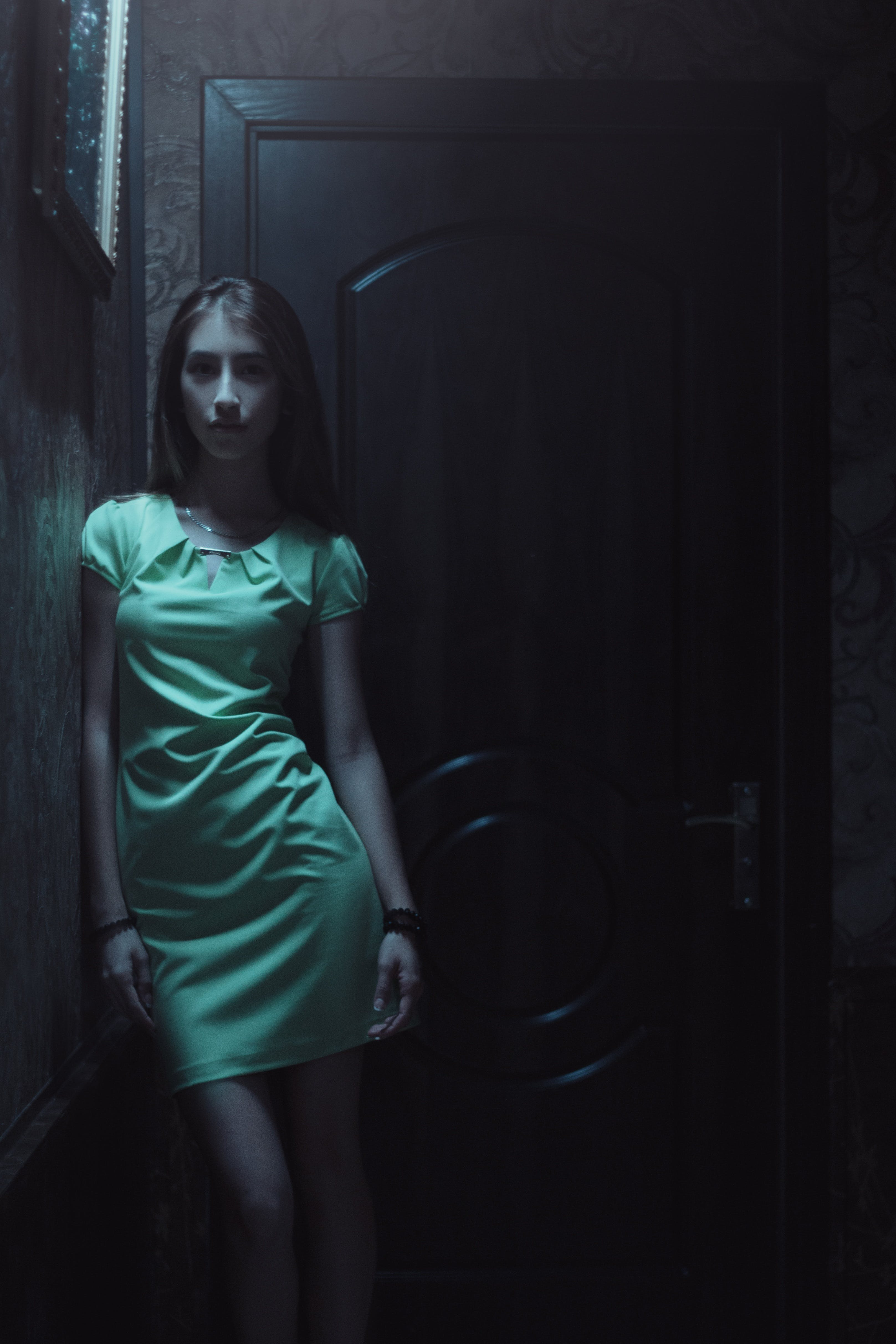 Woman in Green Dress Standing Near Door