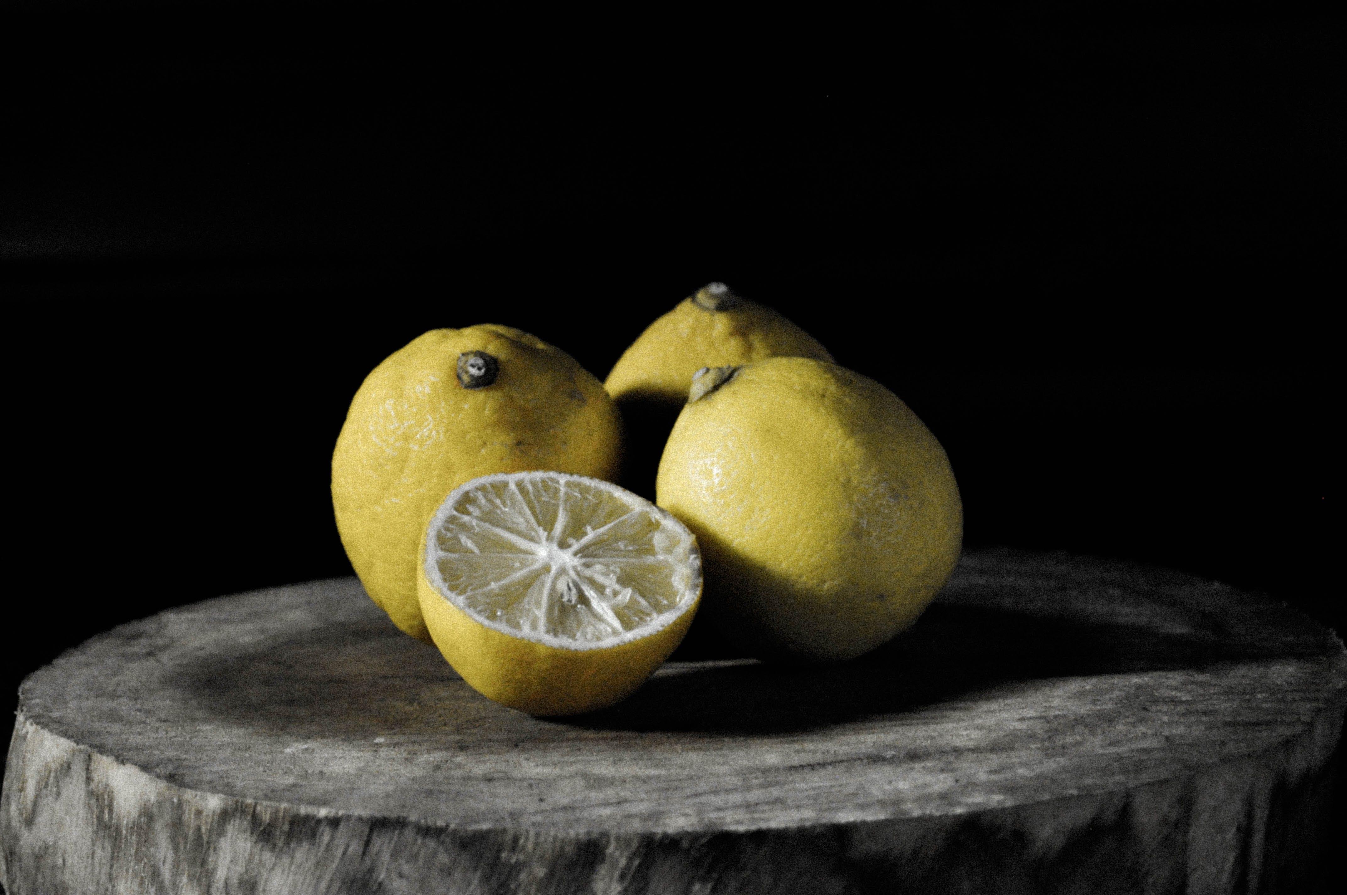 Three Lemons Beside Sliced Lemon on Tree Slab