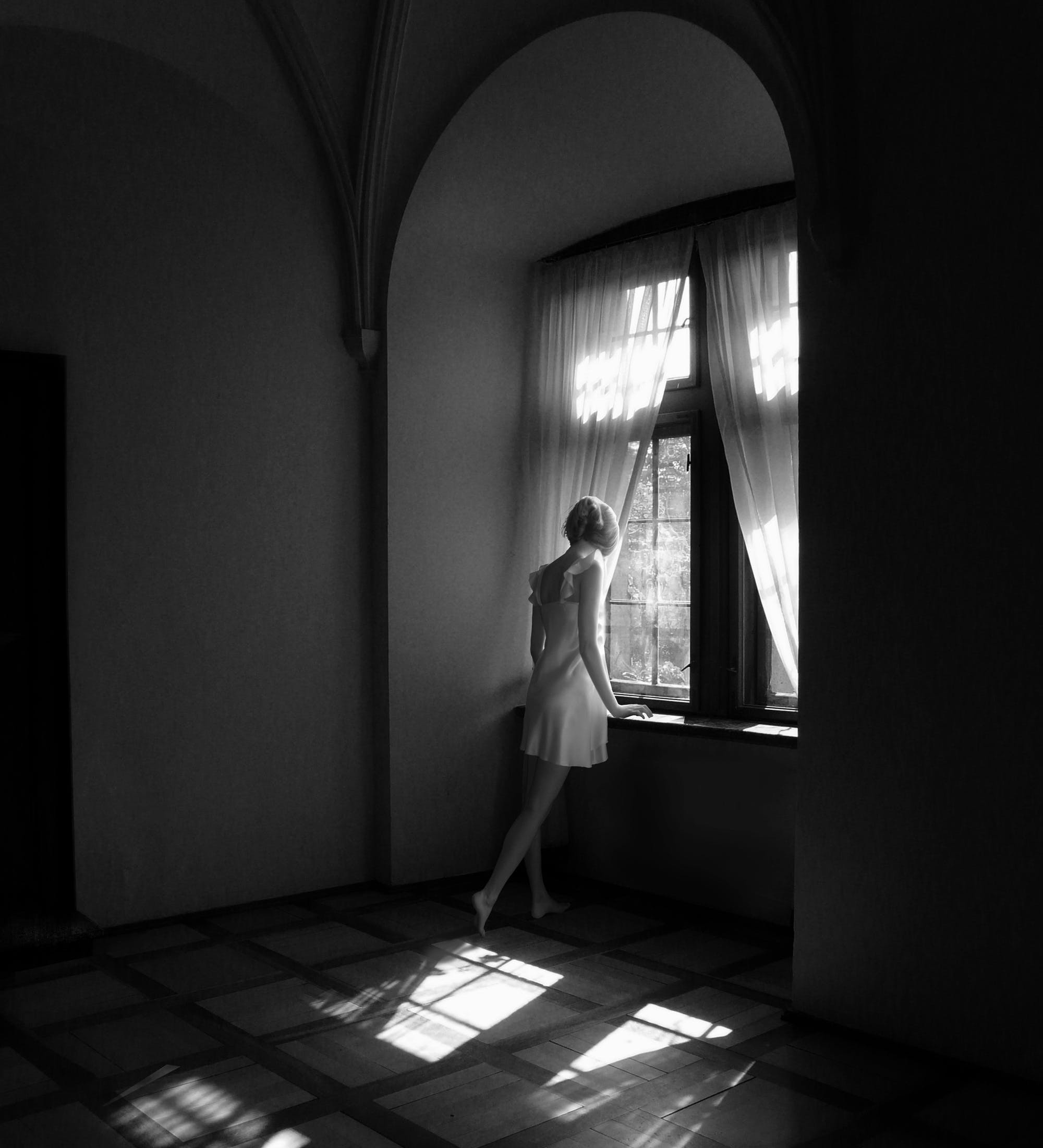 Woman Standing Beside Closed Window Grayscale Photo