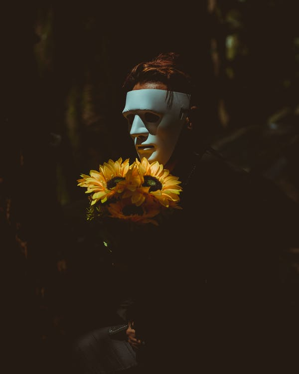 Person Wearing A Mask Holding Sunflowers